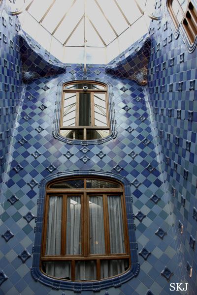 A cylindrical courtyard space lined with blue tiles and a skylight at top in the Batllo, Barcelona. photo by Shara Johnson