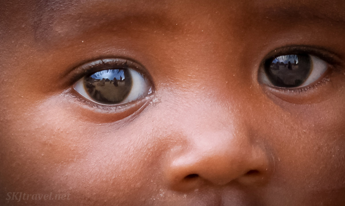 African Witchfinder film crew reflected in a toddler's eyes. Kunene region of Kaokoland, Namibia.