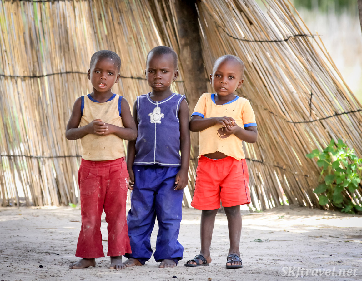 Three little kids standing with a bit of trepidation, checking me out. Caprivi Strip, Namibia.