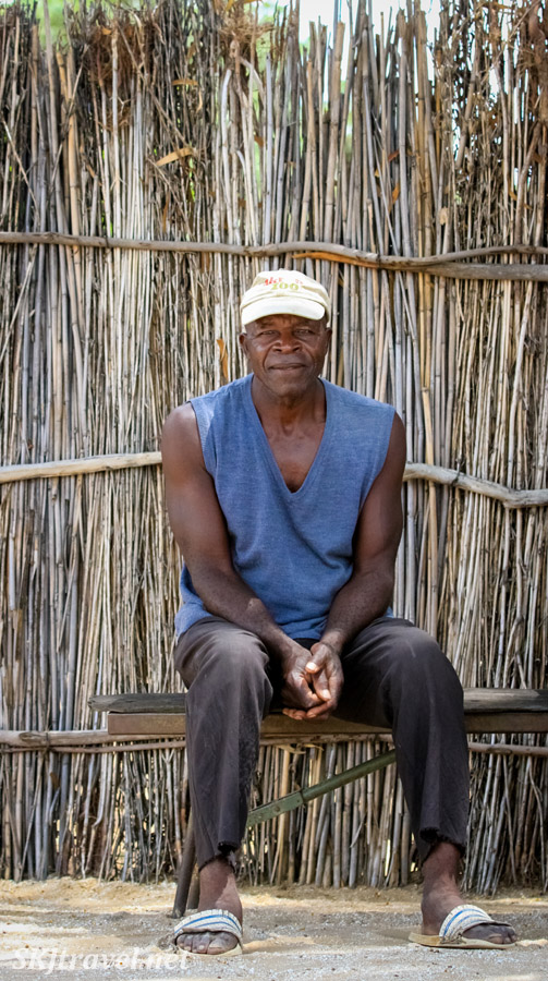 Kavango man sitting waiting for a ride. Caprivi Strip, Namibia.