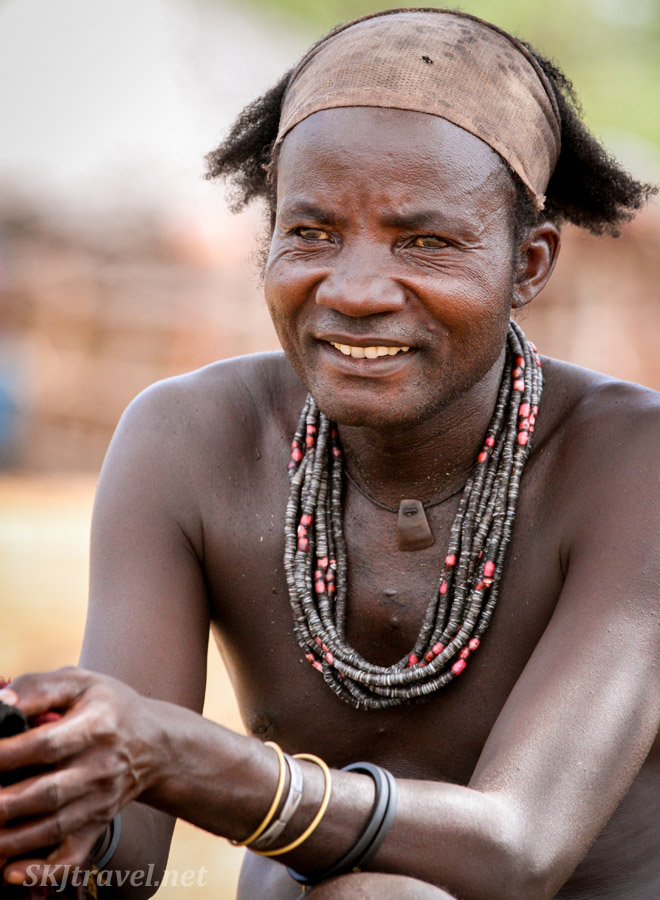Himba man sitting inside his kraal, Kunene region of Kaokoland, Namibia.