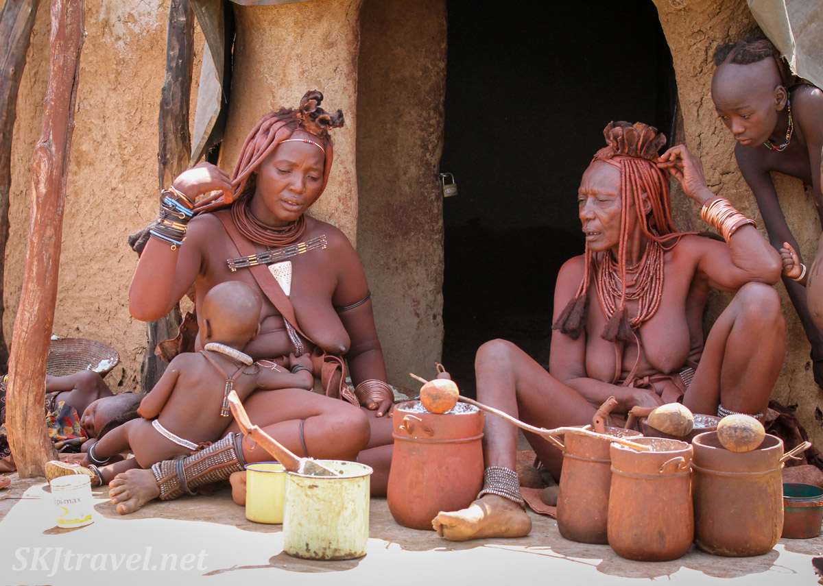 Chief Kapika's eldest and youngest wife outside mud hut in their kraal. Himba people, northern Namibia.