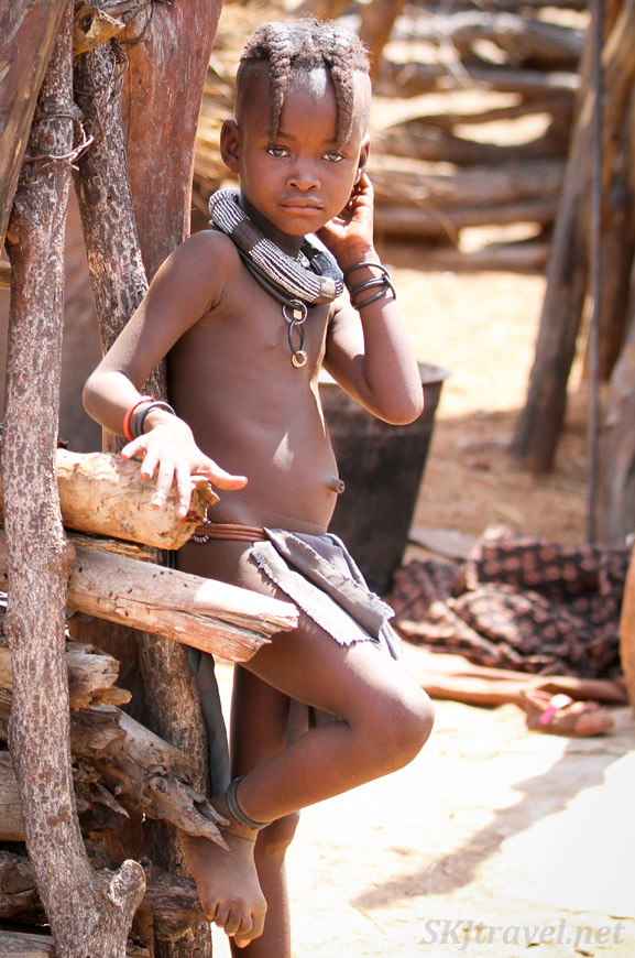 Himba girl standing near her hut in her kraal, northern Namibia, near Epupa Falls.
