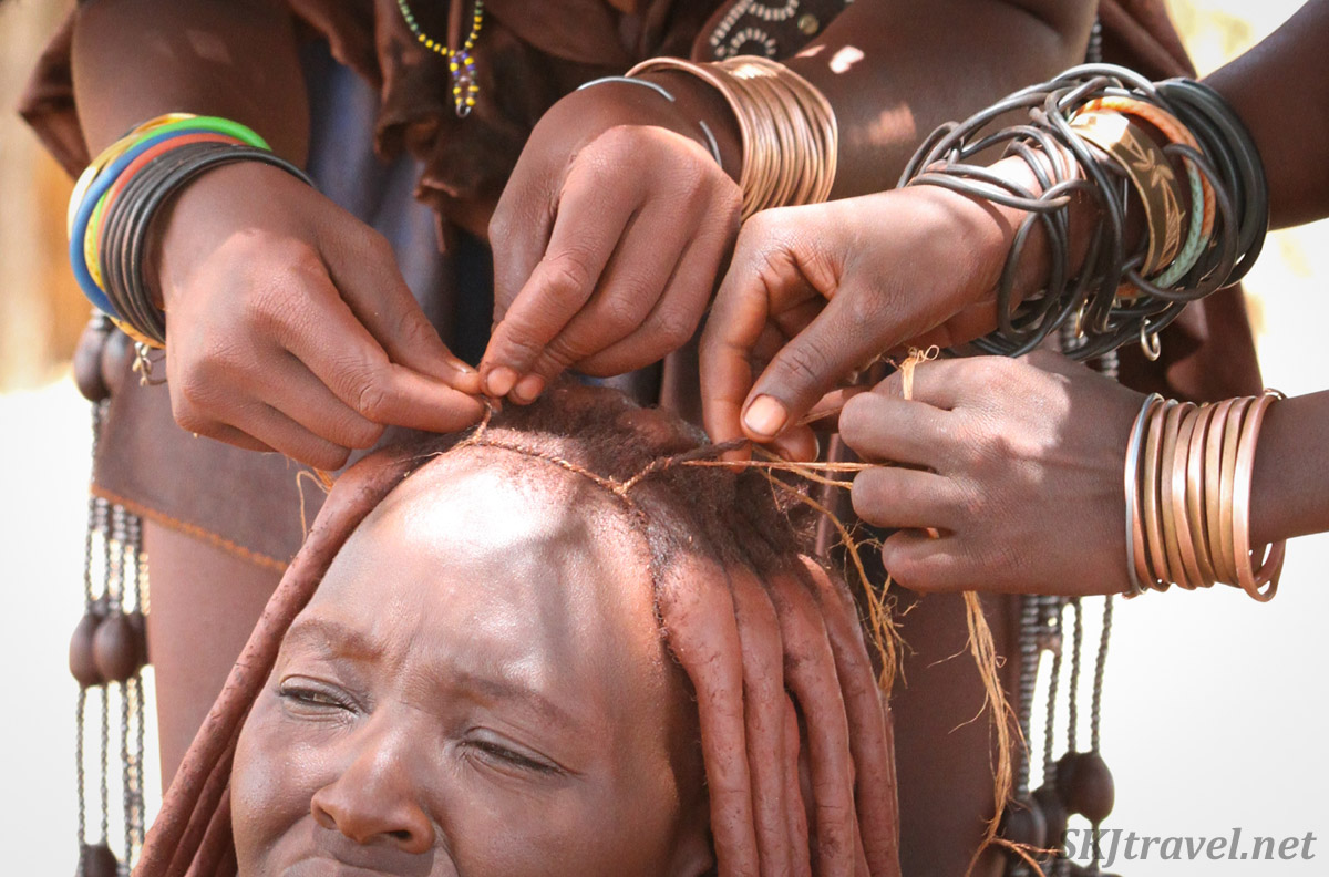 Close up of girls working on the hair of Chief Kapika's youngest wife. Himba tribe near Epupa Falls, Namibia.