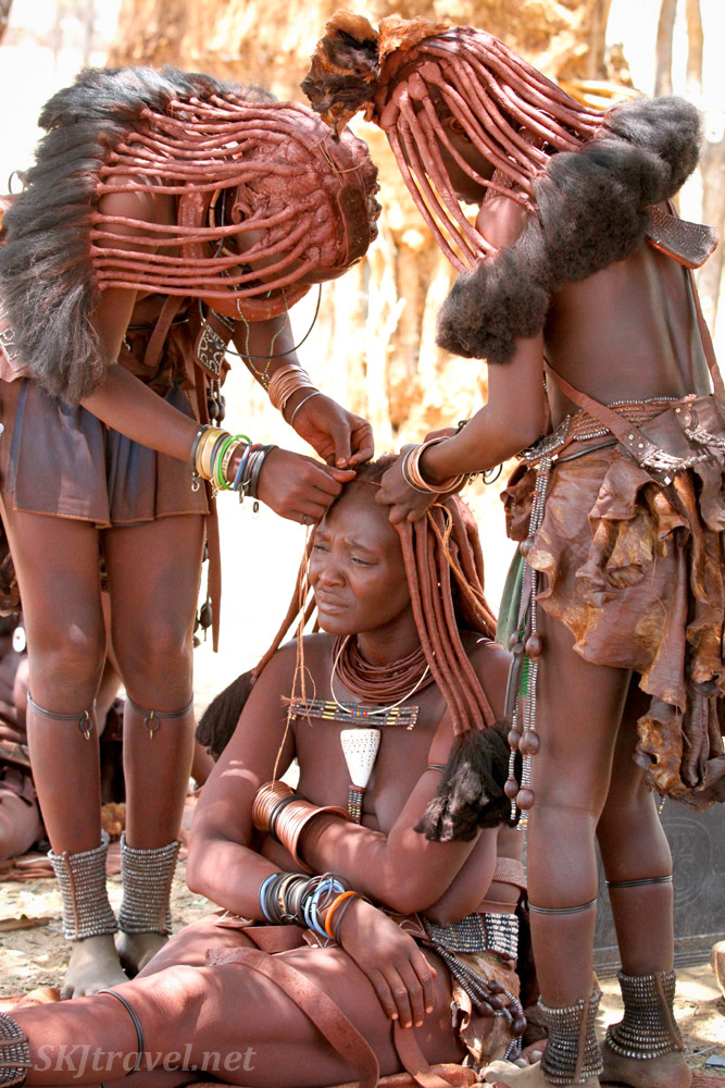 Two girls working on the hairstyle of Chief Kapika's youngest wife. Himba tribe near Epupa Falls, Namibia.