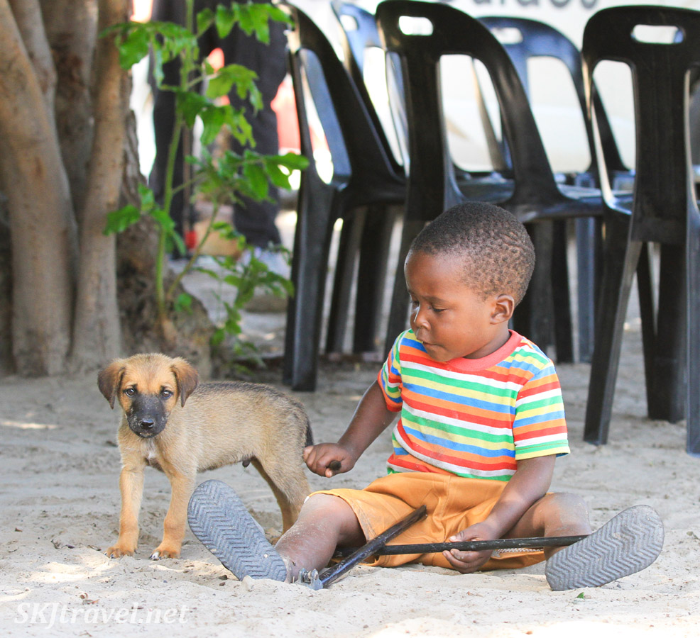 Little boy pulling the tail of his puppy. Chief Joseph, Kake Village, Kavango East, Namibia.