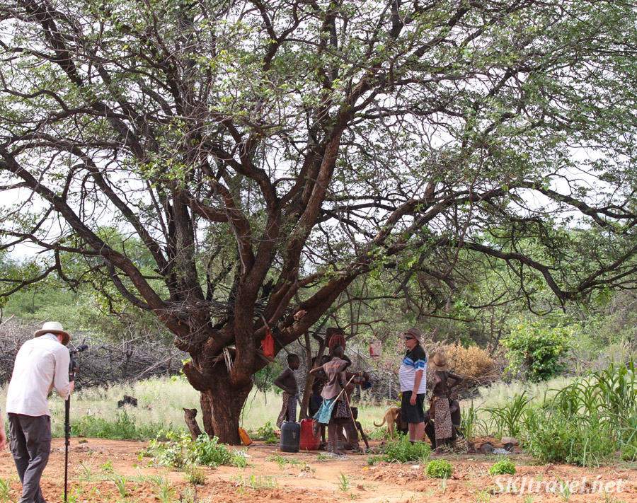 Berrie chatting with Himba youth under a tree outside their kraal. Namibia.