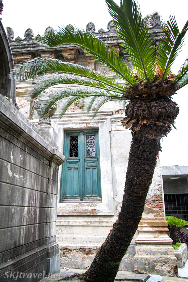 Blue door with palm tree, mausoleum in Recoleta Cemetery, Buenos Aires, Argentina.