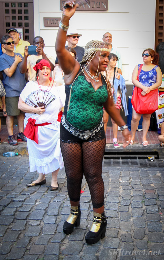 Woman dancing in platform shoes on cobblestone streets in the San Telmo Candombe parade, Buenos Aires, Argentina.