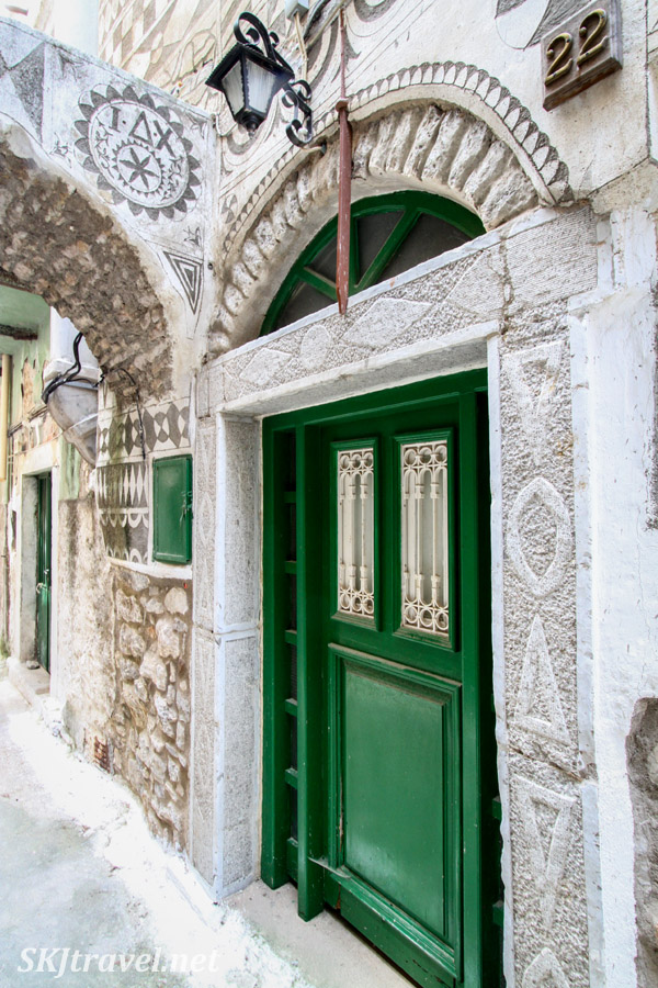 Bright green door in the black and white Xysta facade of the medieval mastic village of Pyrgi, Chios Island, Greece.