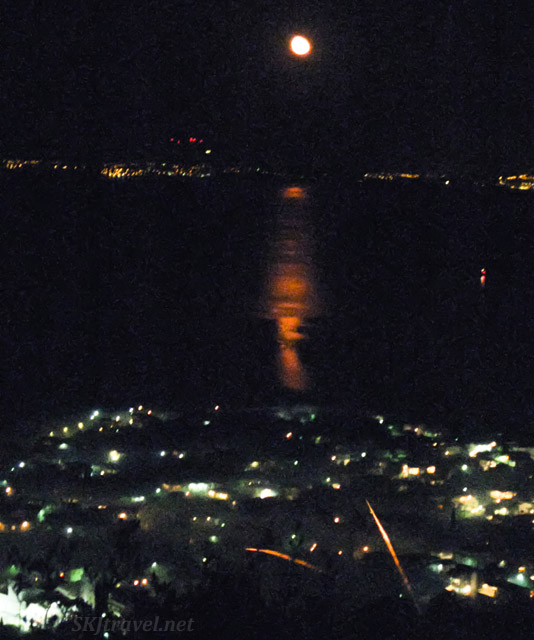 Moon rising over Turkey, reflecting on the Aegean Sea, red from smoke of the Easter rocket wars 2017, Chios Island, Greece.
