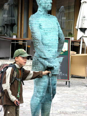 Kid playing with bronze statue fountain. Prague.
