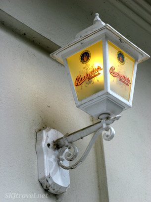 Outdoor lamp with Budweiser written on the glass