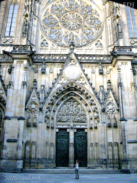 I am dwarfed beside the St. Vitus cathedral early in the morning with a nearly empty courtyard. Prague.