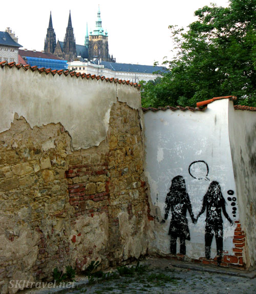Graffiti of people holding hands on an alley wall in Prague.