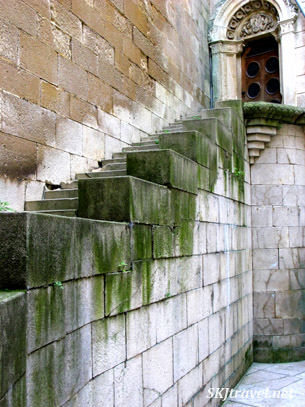 Mossy stairs leading up to a wooden door in stone castle.