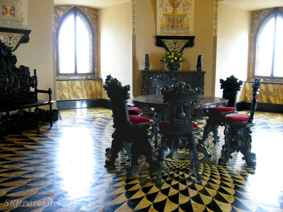 yellow and black tiled floor with elaborate wood carved chairs and table