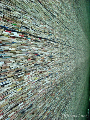 Standing at the end of a corridor of what looks like million of books, an illusion using mirrors.