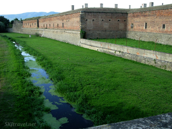 grass covered moat outside brick building