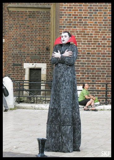 Man dressed as a vampire, standing still like a statue for money in market square, Krakow, Poland.