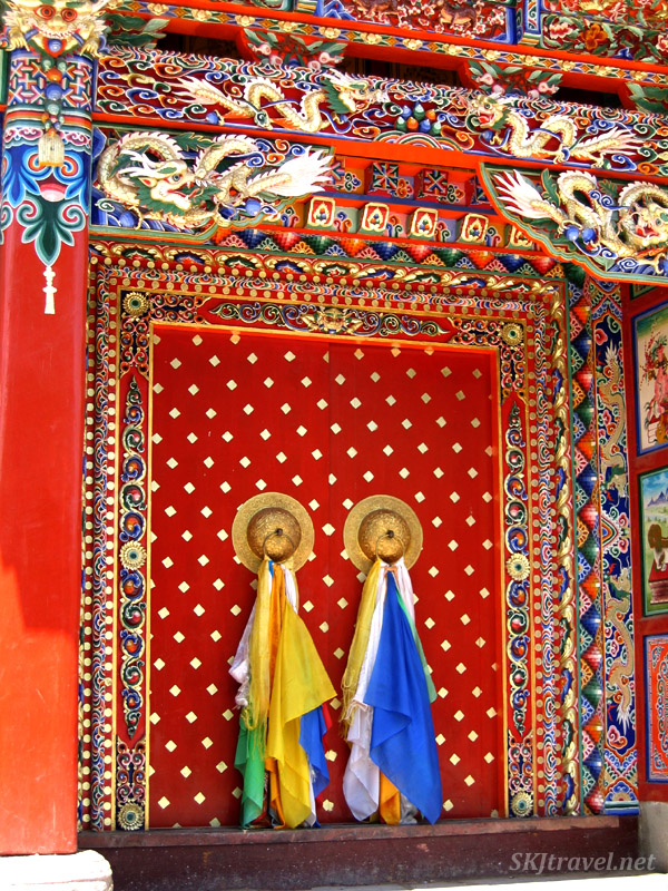 Very brightly painted doorway with colorful scarves tied to the doorknobs. Labrang Monastery, Xiahe, China.