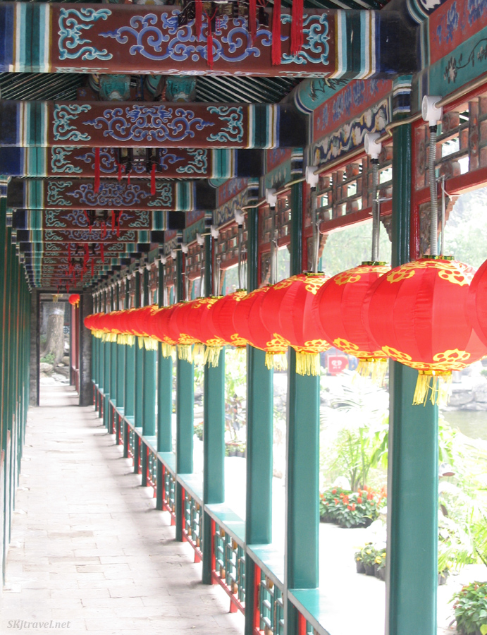 Red paper lanterns line a corridor with green poles and colorful rafters. Photo by Shara Johnson