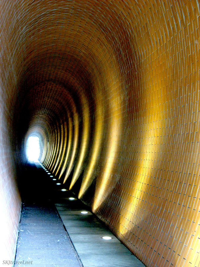 A simple tunnel made of bricks in a woven patterh is lit by yellow lights at regular intervals shining onto the curved walls. Photo by Shara Johnson