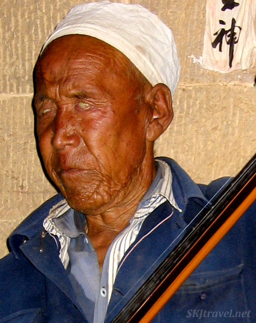 Head shot of a blind musician inside a courtyard in Shaanxi Province, China. Dang Jiashan village. Photo by Shara Johnson
