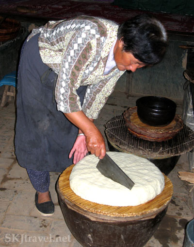 Woman cutting through a cake of fresh tofu with a cleaver, in a village in Shaanxi Province, China. Photo by Shara Johnson
