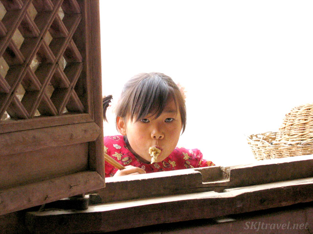 Young girl eating noodles in a window of a yao in the rural village, Dang Jiashan, Shaanxi Province, China.