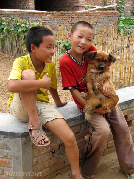 Boys with their puppy in the new, relocated Dang Jiashan village in the valley, Shaanxi Province, China.