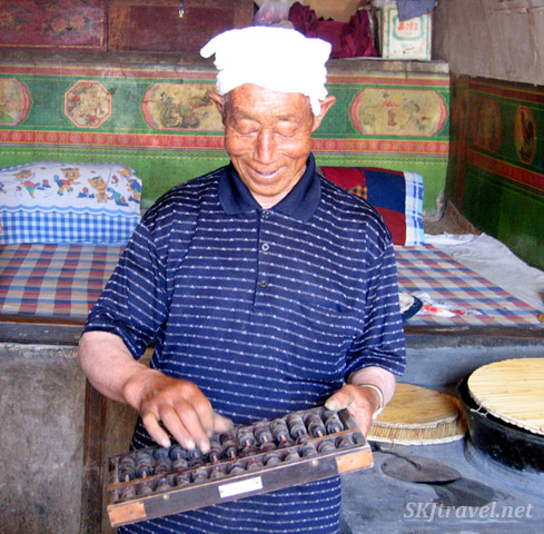 Papa demonstrating the use of an abacus for accounting. Dang Jia Shan village, Shaanxi Province, China.