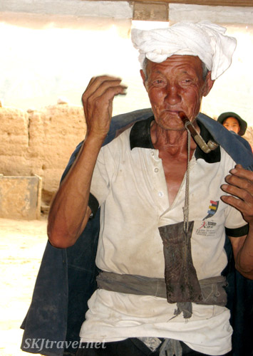 Old man with pipe and homegrown tobacco. Dang Jia Shan village, Shaanxi Province, China.