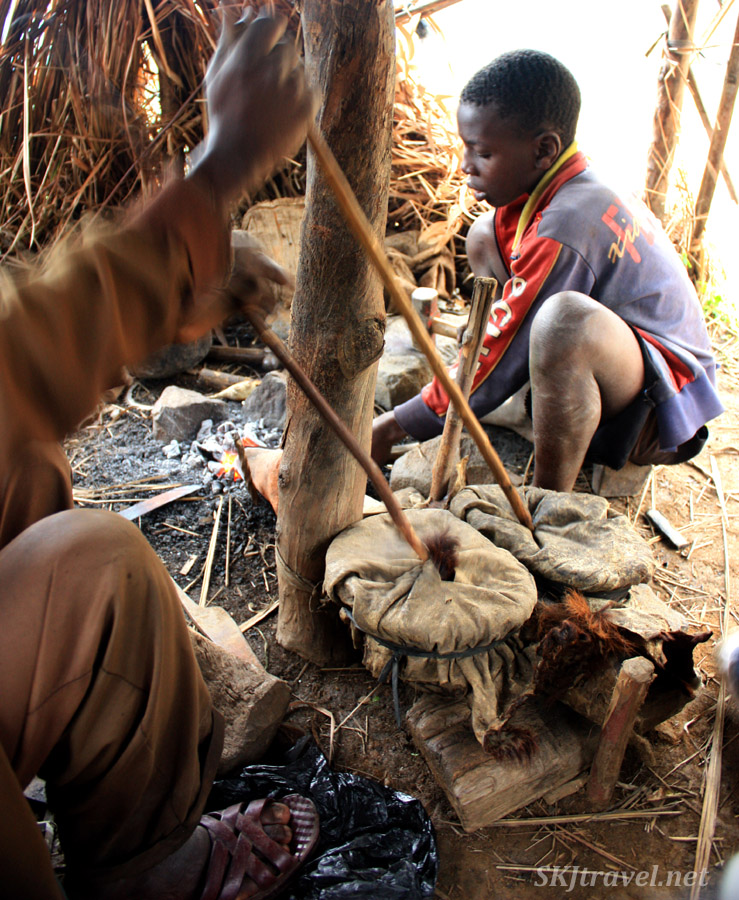 Using a sheepskin bellows to stoke the fire soft metal ... blacksmith in the lower Rwenzori Mountains, Uganda.