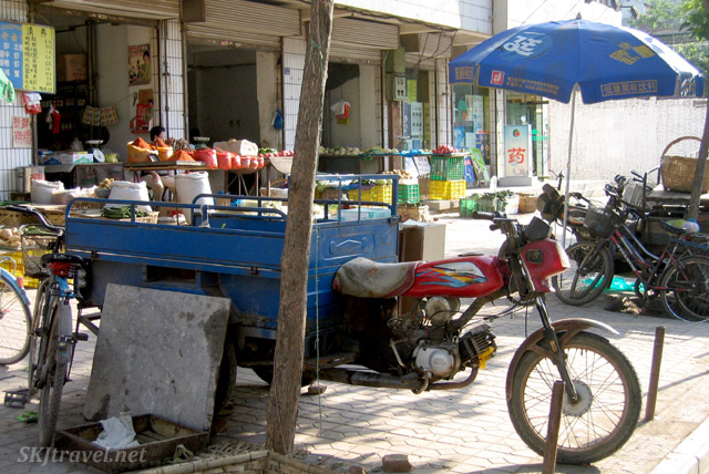 Motorcycle cart parked in front of a sidewalk full of spices for sale in the Muslim Quarter of Xian, China.