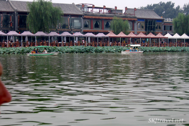 Erik's nose, plus restaurant tables lining the sidewalk and small boats on the Back Lakes in Beijing, China.