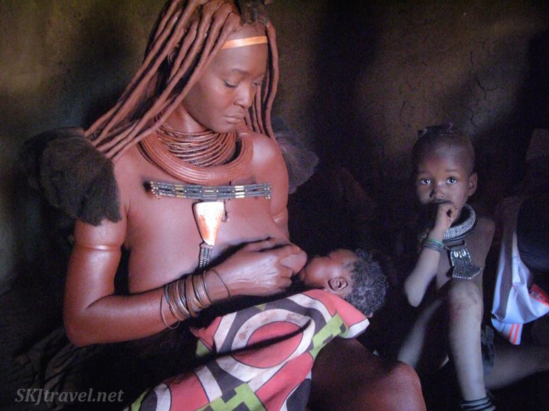Himba mother suckling a newborn, Kaokoland, Namibia.