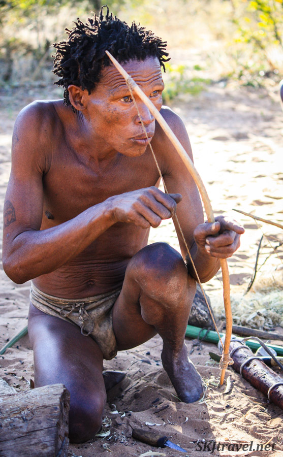 San bushman demonstrating how to make and use a bow. Namibia.