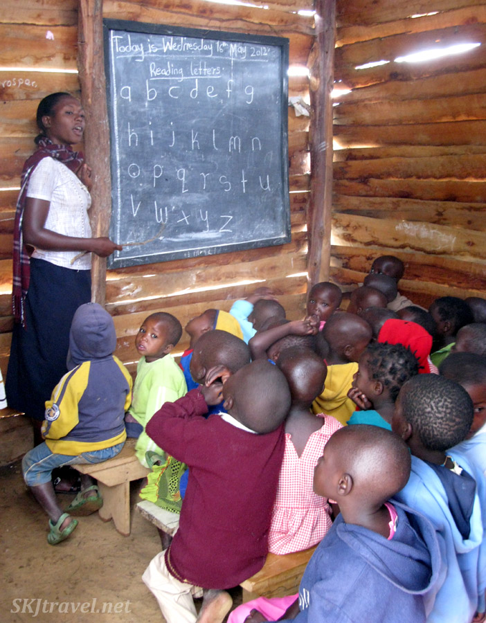 School children crammed into a small room with the teacher using a stick at the chalkboard, learning English. Lake Bunyoni, Uganda.