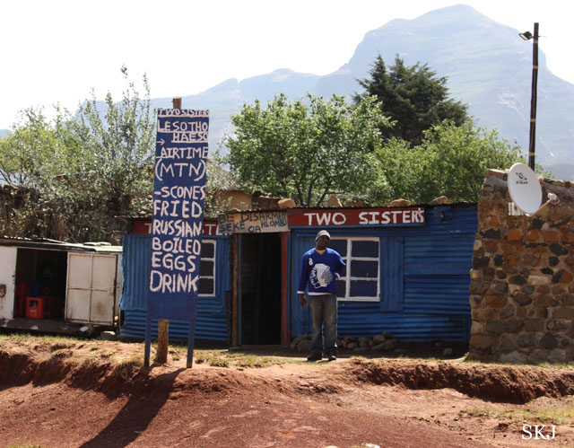man standing outside building with list of groceries on a sign. Lesotho