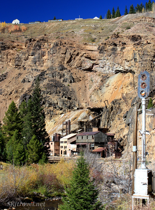Buildings of the ghost town of Gilman, Colorado, perched at the edge of a cliff over the train station in the valley.