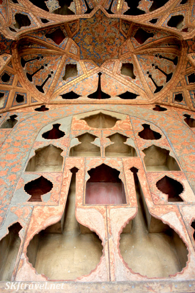 Detail of shapes of carved hollow spaces into painted wooden ceiling inside Ali Qapu, Isfahan, Iran.