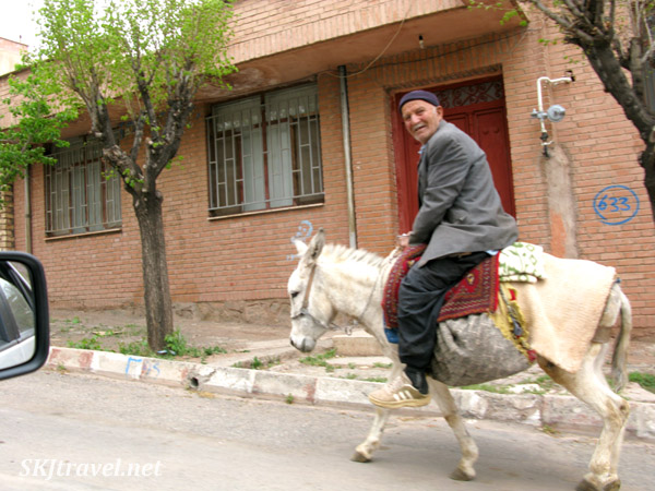 Man on a white donkey races us in our car through the streets of Abyaneh village, Iran.