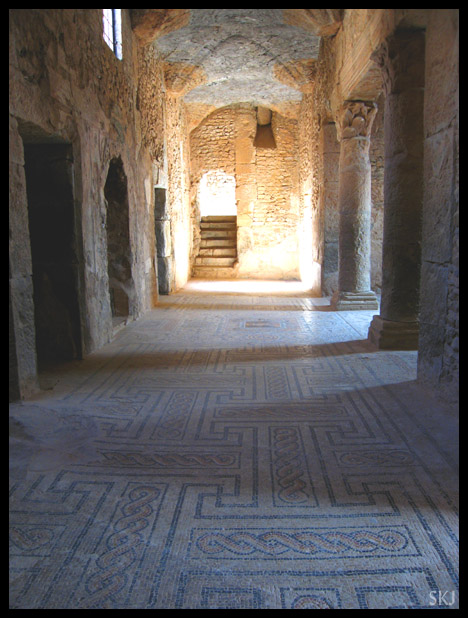 Inside a long corridor with ancient roman tile mosaic on the floor, a doorway and stairs at the end of the corridor in Bulla Regia Tunisia. photo by Shara Johnson