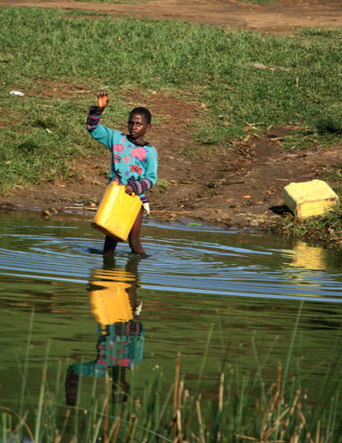 Child filling water can in Kazinga Channel, Queen Elizabeth NP Uganda