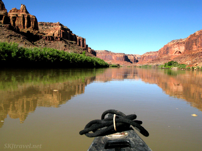 Pointed downriver in our canoe with reflections of the canyon walls on both sides of the still water. Green River, Utah.
