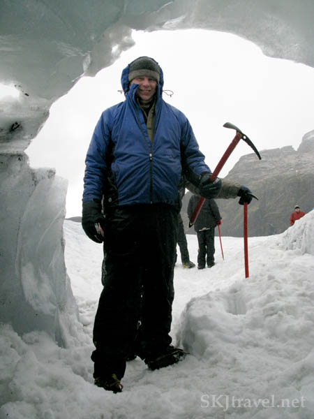 man standing in an ice tunnel
