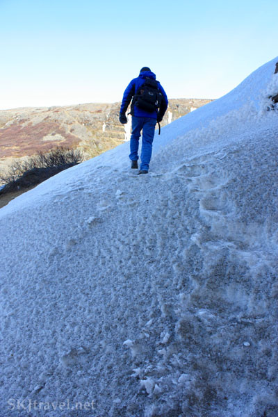 Man crossing a snow patch on a steep hillside, Glymur Falls, Iceland. Photo by Shara Johnson