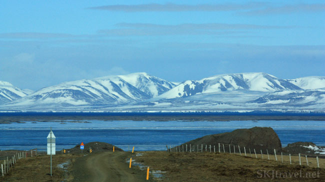 Scene through a car windshield of dirt road leading toward ocean with snow-capped hills, Iceland. Photo by Shara Johnson