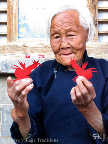 Elderly woman in Shaanxi Province, China, display paper cuttings of two birds she just cut. Photo by Shara Johnson